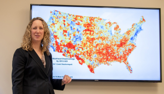 Dr. Amy Kind with a display of the Neighborhood Atlas map. Credit: Clint Thayer/Department of Medicine